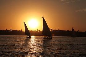 Sunset scene on the Nile from Nile Dahabya showing two sails in the skyline
