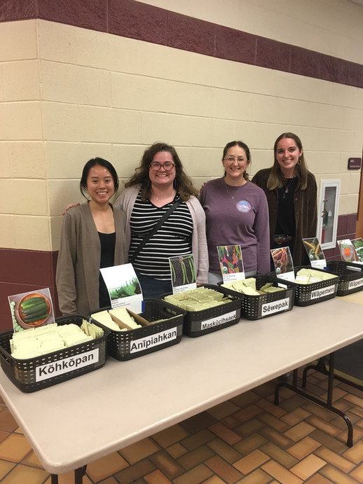 AIHEC VISTAs help out at a CMN seed giveaway organized by one of the members.