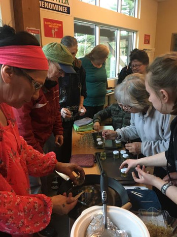 """""""Plants are medicine"""" workshop at CMN organized in part by the CMN VISTA. The workshop leader explains the benefits of the Calendula flower and how to create one's own salve and lip balm from it."""