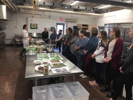 At UTTC, a VISTA teaches an indigenous cooking class at the Land Grant office for members of the North Dakota Nutrition Council. The menu includes wojapi made from locally harvested juneberries, corn bannock made from corn grown at the college, bison jerky made from local bison, a dandelion salad made from foraged greens, and native beans which were grown on campus and cooked with foraged cedar and juniper berries.