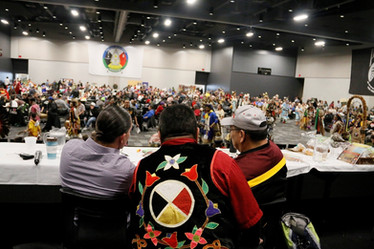 13 Moons Gichi Manidoo Giizis Pow Wow, Jan 12th, 2019. From left to right: Nick Hanson (Ojibwe Language Translator), Ricky Defoe (Spiritual Advisor), Les Gibbs (Emcee). The annual Pow Wow brings people together who take care of the land and community.  Photo credit: Ivy Vainio