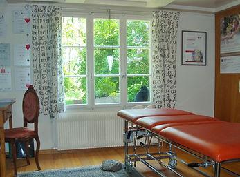 Schmerztherapiepraxis LiebschrundBracht behandlungsliege braunes Leder, Fenster mit Blic in grünen Garten