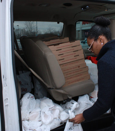 Shatoyia Moss organizes meals donated from Longhorn Steakhouse and Pizza X