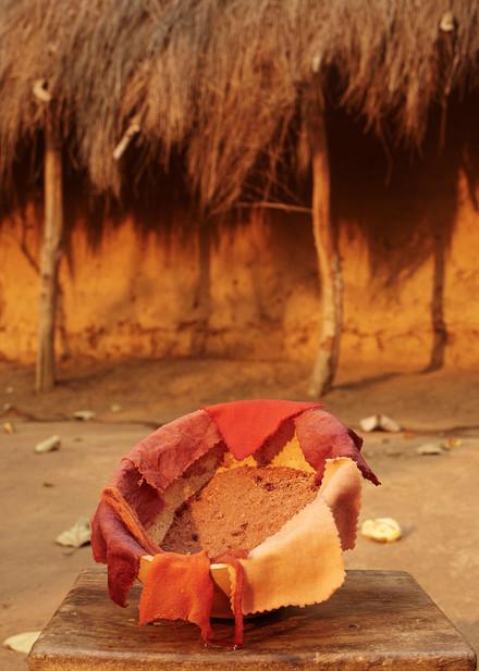 Madder root dyed textiles outside hut, Modiya