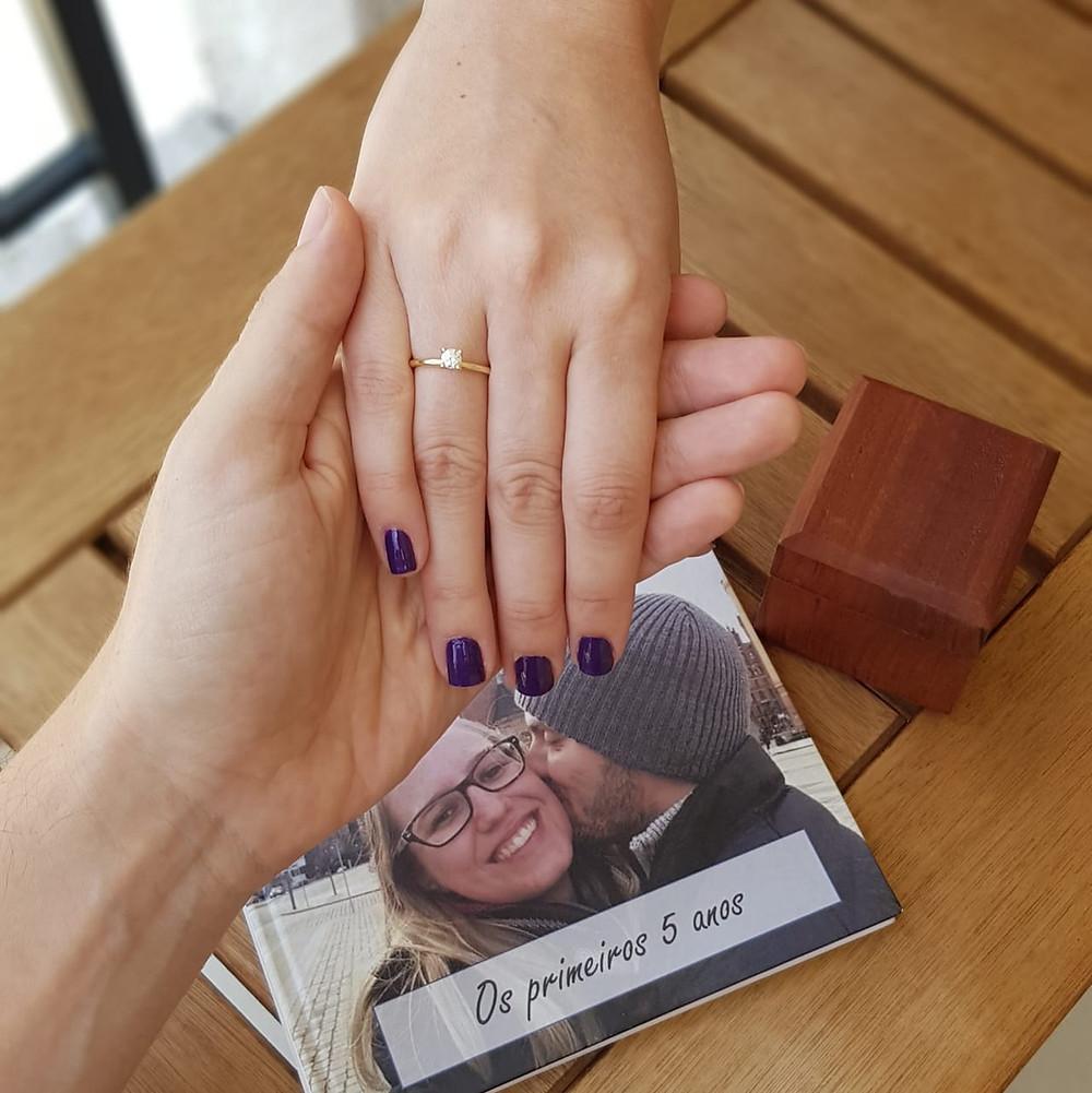 foto das mãos do noivo e da noiva, a dela com o anel de noivado e o livro produzido