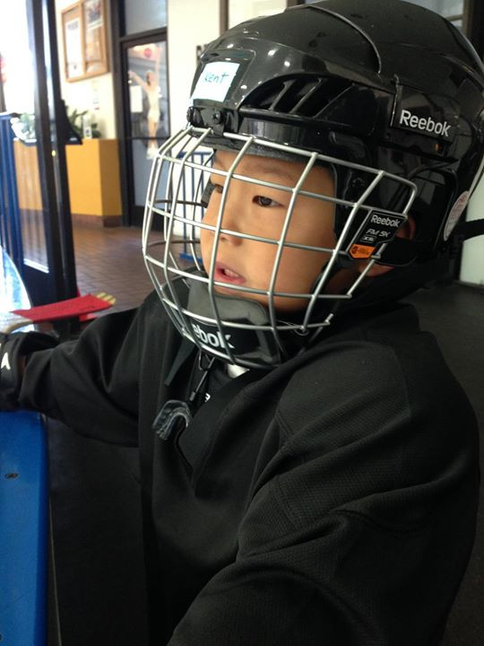 Kent in his hockey helmet. The chin strap goes under his chin and snaps on the other side. The side straps each go back and snap near the temples.