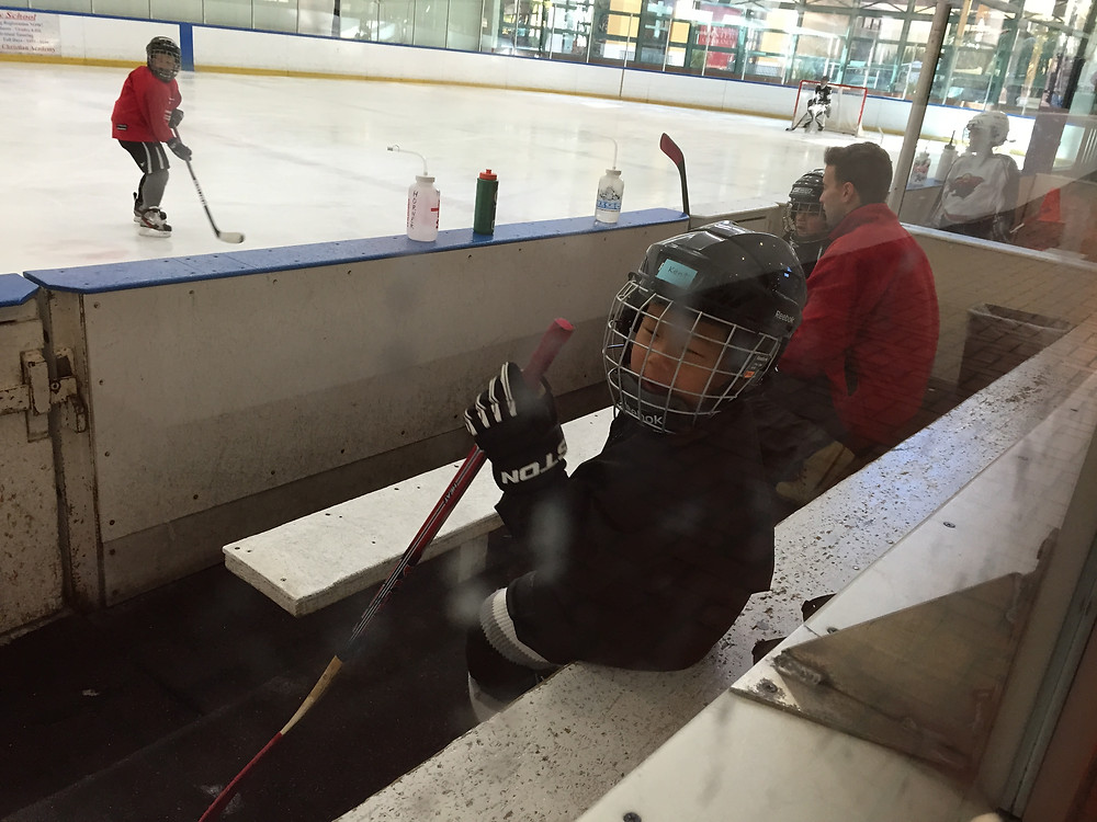 Kent in the penalty box, wearing his black helmet, jersey, pants, and gloves.