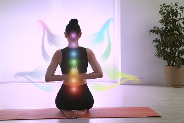 Young woman with chakra points practicing yoga in studio, back view. Healing energy .jpg