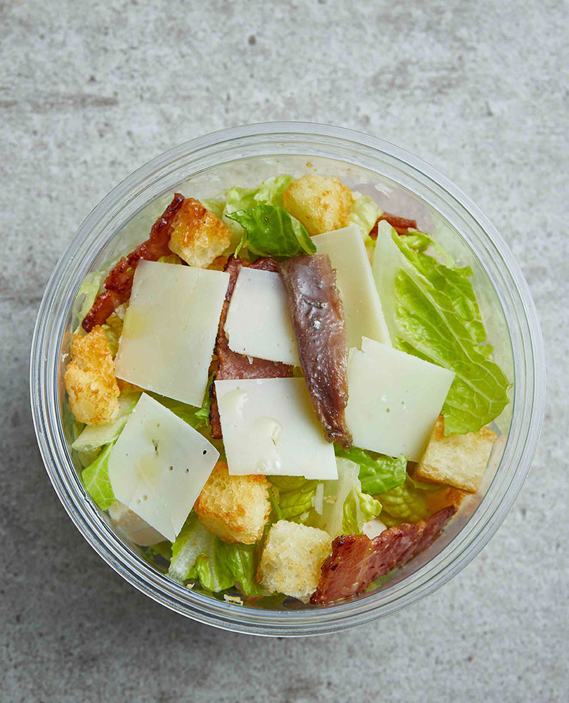 CAESAR SALAD Romain lettuce is the important part of this crispy salad. Mixed with moist chunks of chicken, bacon and crunchy croutons.  Pain Chaud's Caesar salad has a dressing made with red wine vinegar giving it a refreshing, tangy twist.