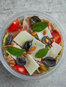 PESTO PASTA SALAD Al denté cooked shell pasta with fresh cherry tomatoes together with roasted tomatoes, green and yellow zucchini's, slices of Parma ham, pieces of fragrant Parmesan cheese and finally a dressing made of pine nuts, black olives and a touch of basil.