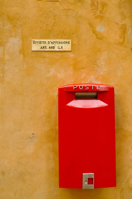 Red postbox on a yellow wall in Volterra