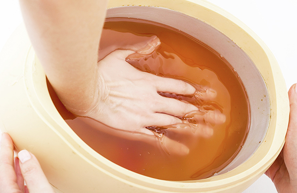 hand_dipping_into_a_paraffin_wax_machine_jpg-600x390