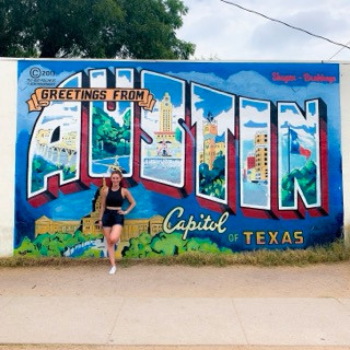 "Standing in front of the ""Welcome to Austin"" mural"
