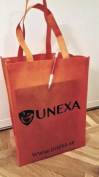 Orange rektangulär tygpåse med företagsnamn och logga i svart. Orange penna satt på påsens kant.