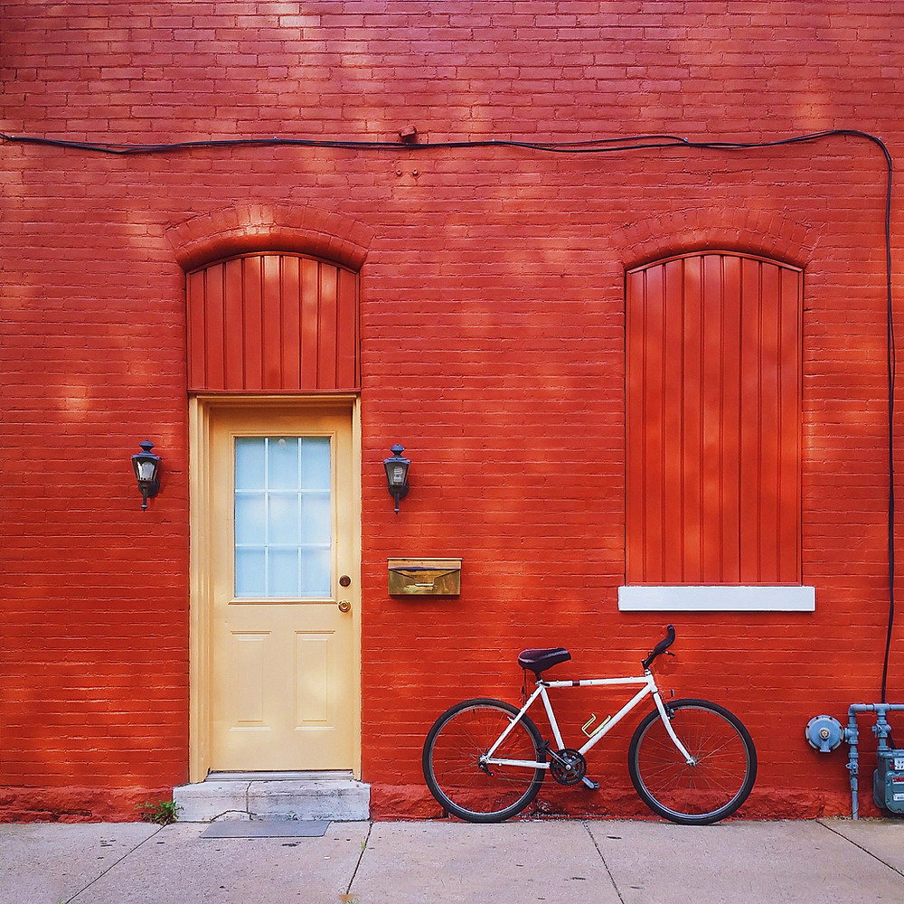 Red brick wall with a yellow door, wooden mail box and a white mens bike leaning. From novaleewilder.com Blog on Numerology and House Numbers