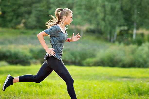 lady with ponytail in grey top and black leggings running in green field