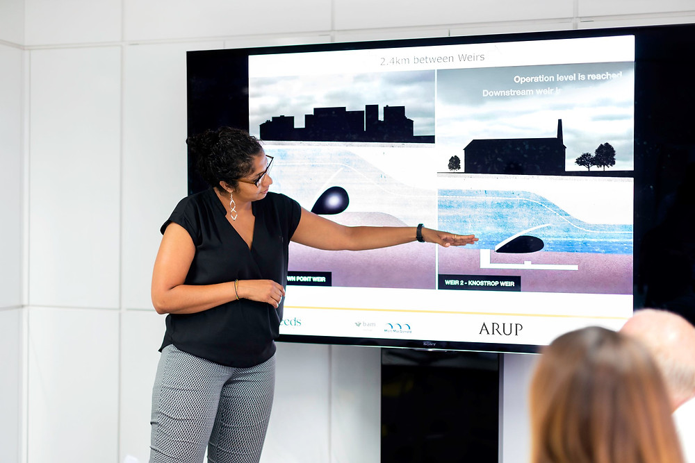 confident women presenting and pointing at a screen in ARUP
