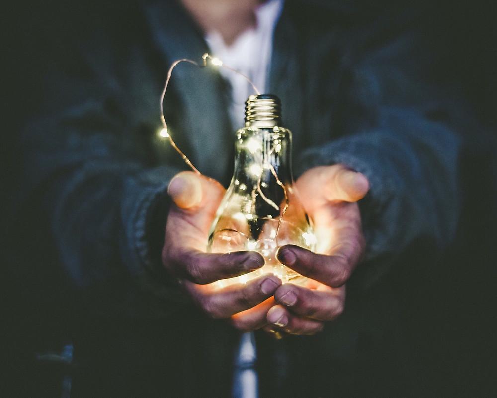 Man in denim jacket holding a glowing lightbulb