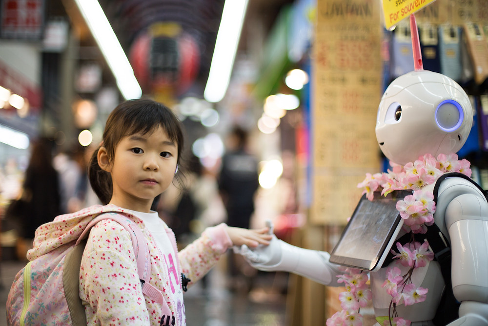 small Asian girl holding hands with a robot