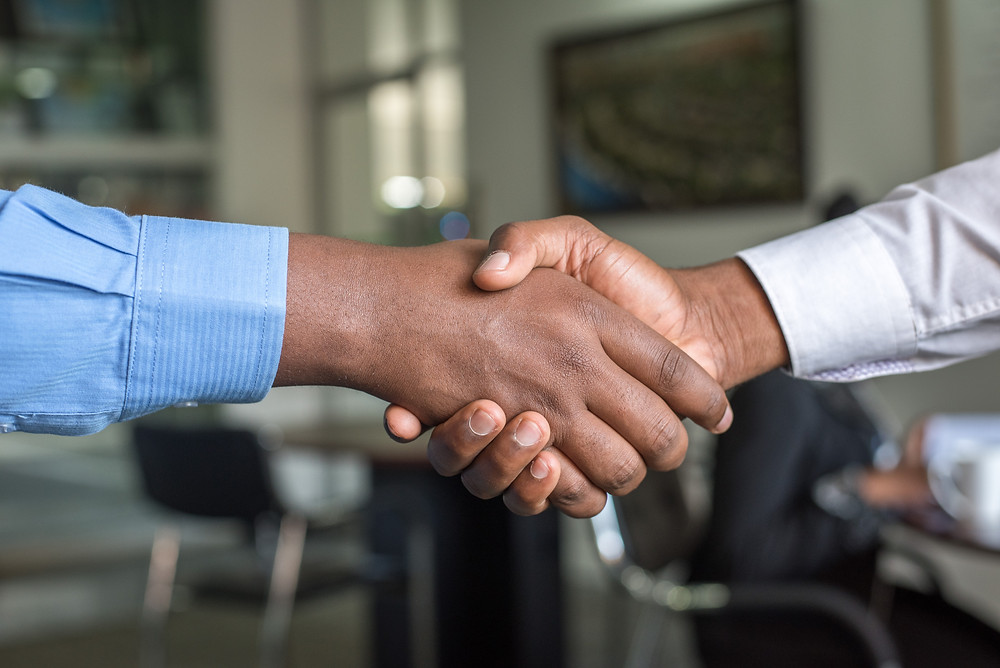 Shaking hands of two men of colour with shirt cuffs