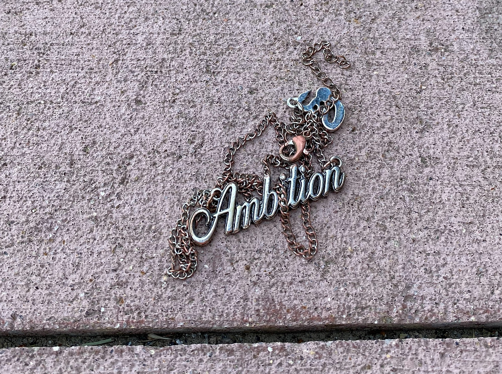 blue, silver and pink Ambition necklace on concrete