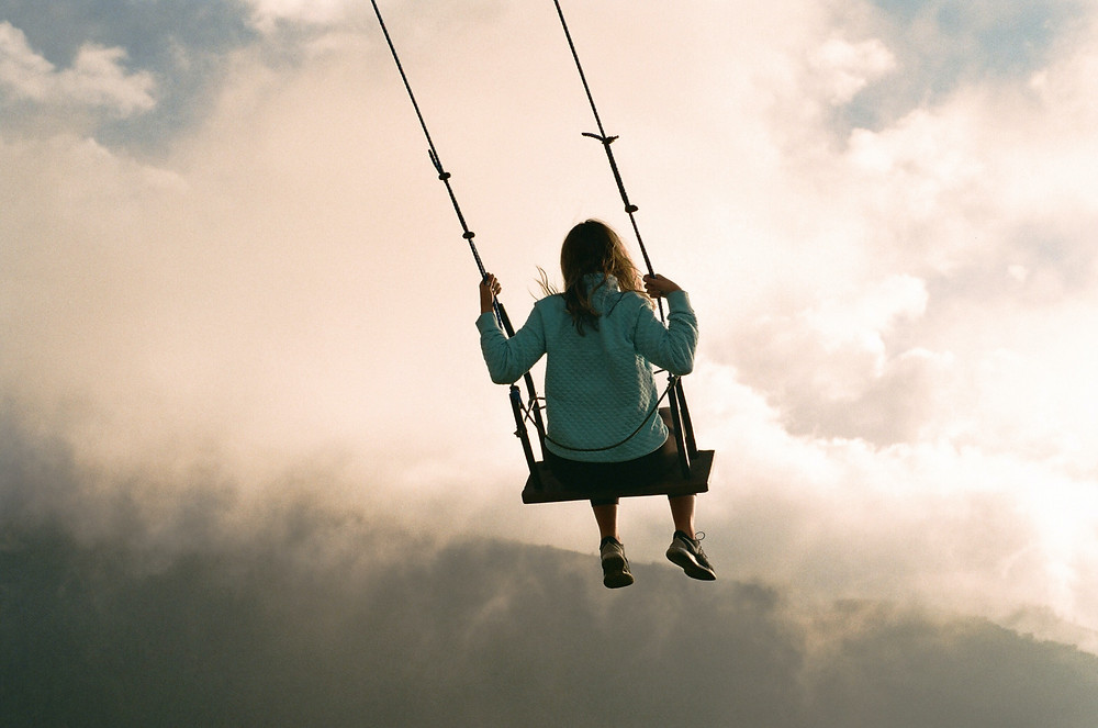 female switching off from work on a swing