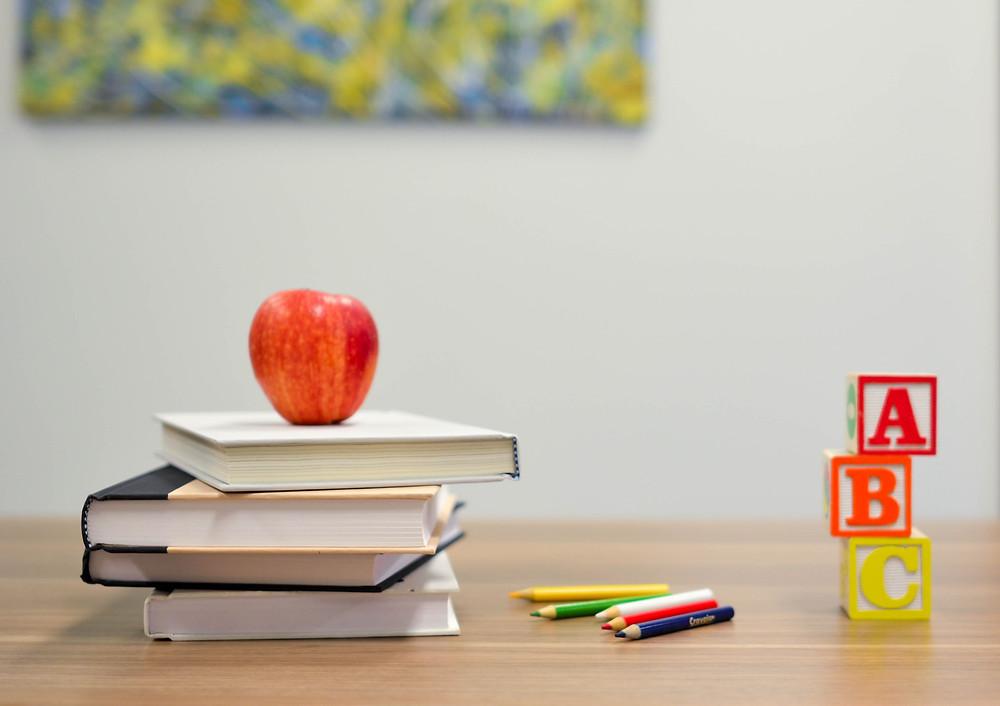 apple on three books and ABC blocks on a school desk