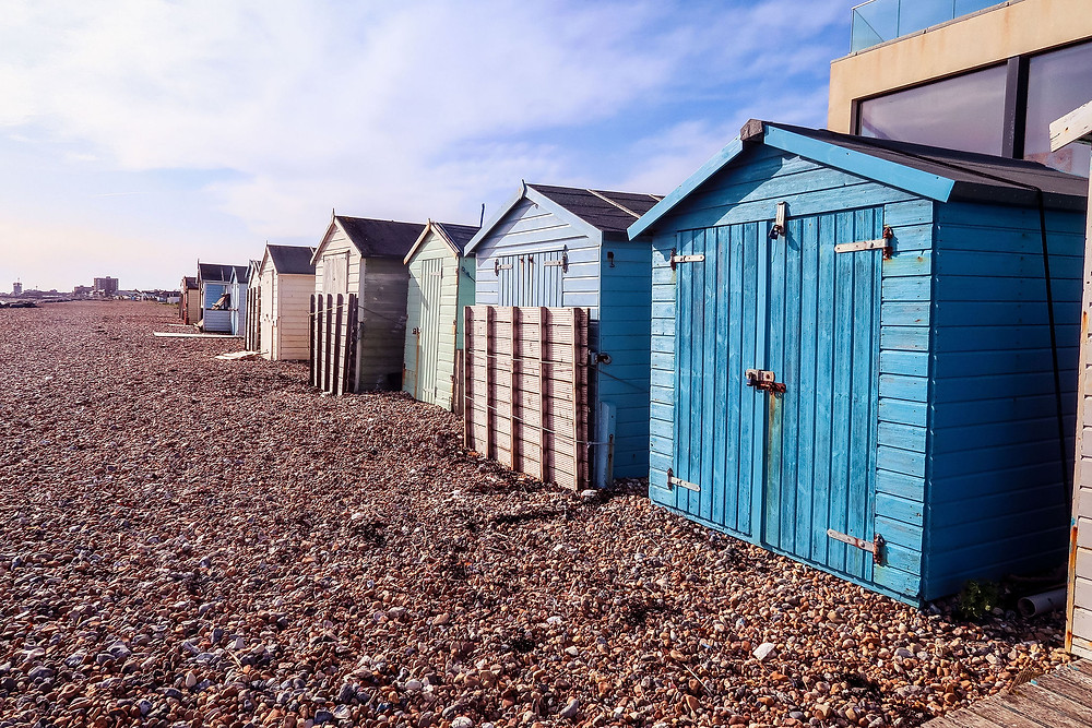 row of blue and green beach huts on pebble beach