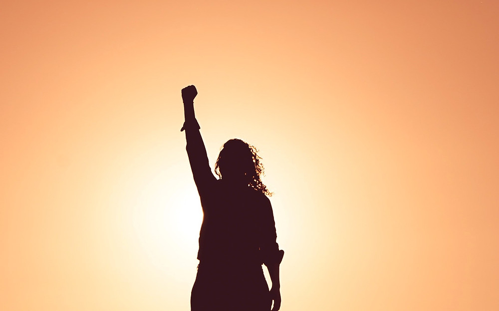 silhouette of person with long hair raising left arm against sunrise