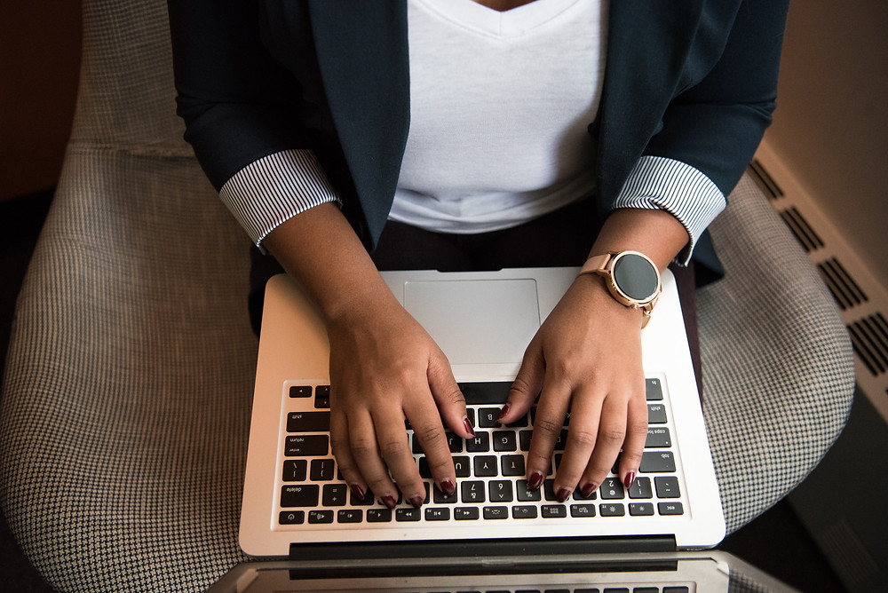 picture of business woman hands sat on a chair and typing on a laptop