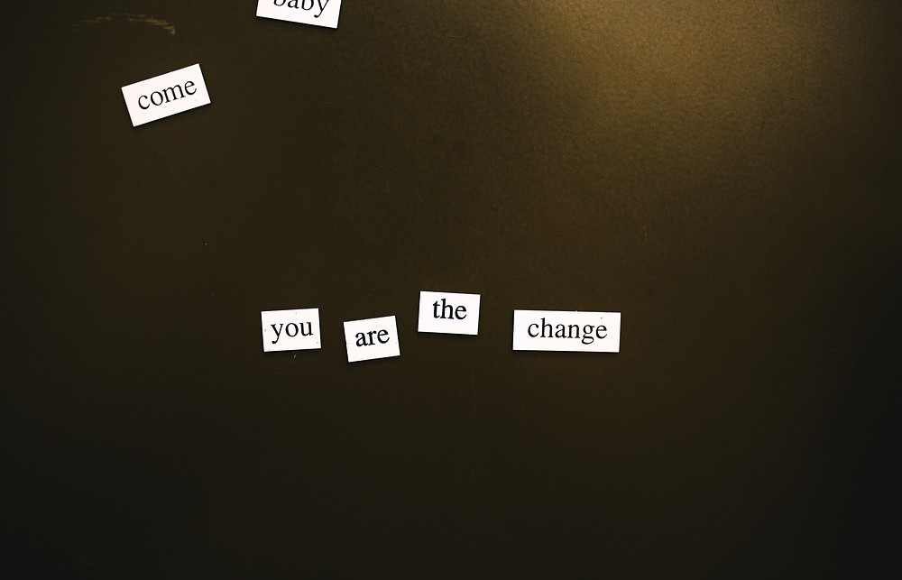 """white word tiles spelling """"you are the change"""" on a dark background"""