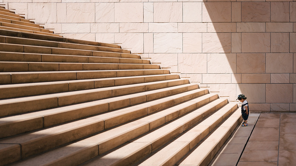 small toddler at the bottom of a large flight of stairs with sunlight beaming down