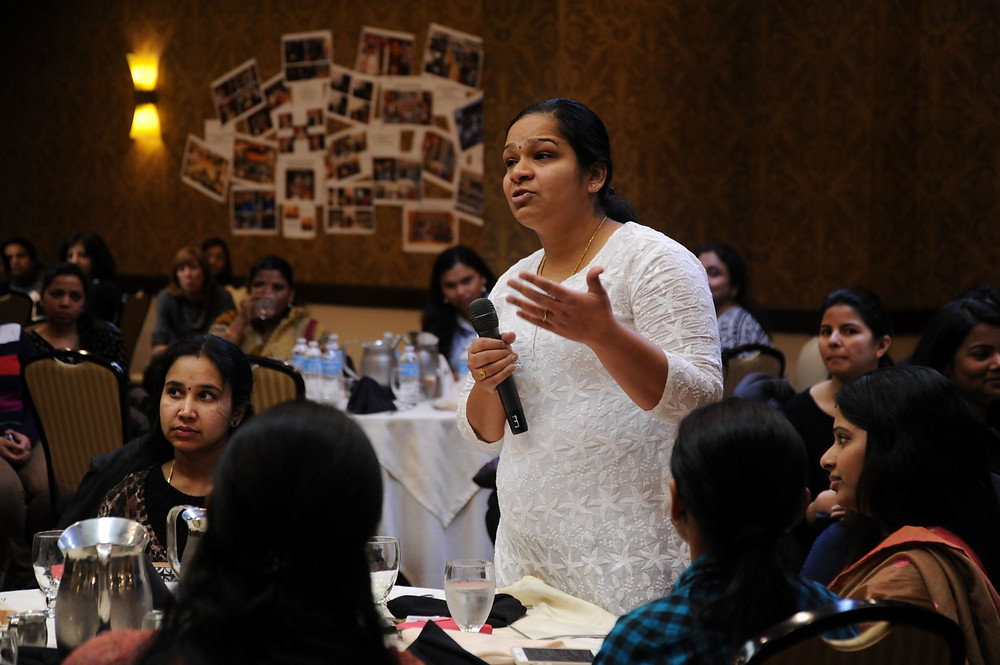 confident Indian woman speaking with microphone at a conference