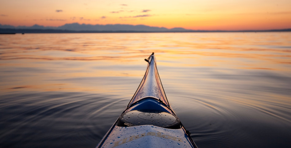 Bow of sea kayak at sunset pointed at Ba