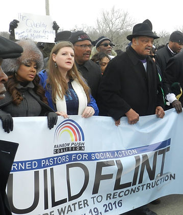 Religious leaders lead a march holding a banner saying: Rainbow Push Coalition, Rebuild Flint