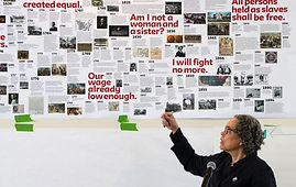 Mindy Fullilove points to a timeline of inequality taped to the wall behind her.
