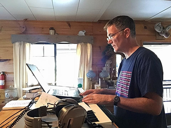 Victor Labenske writing the Sunday Morning Christian Hits Companion at the cabin.