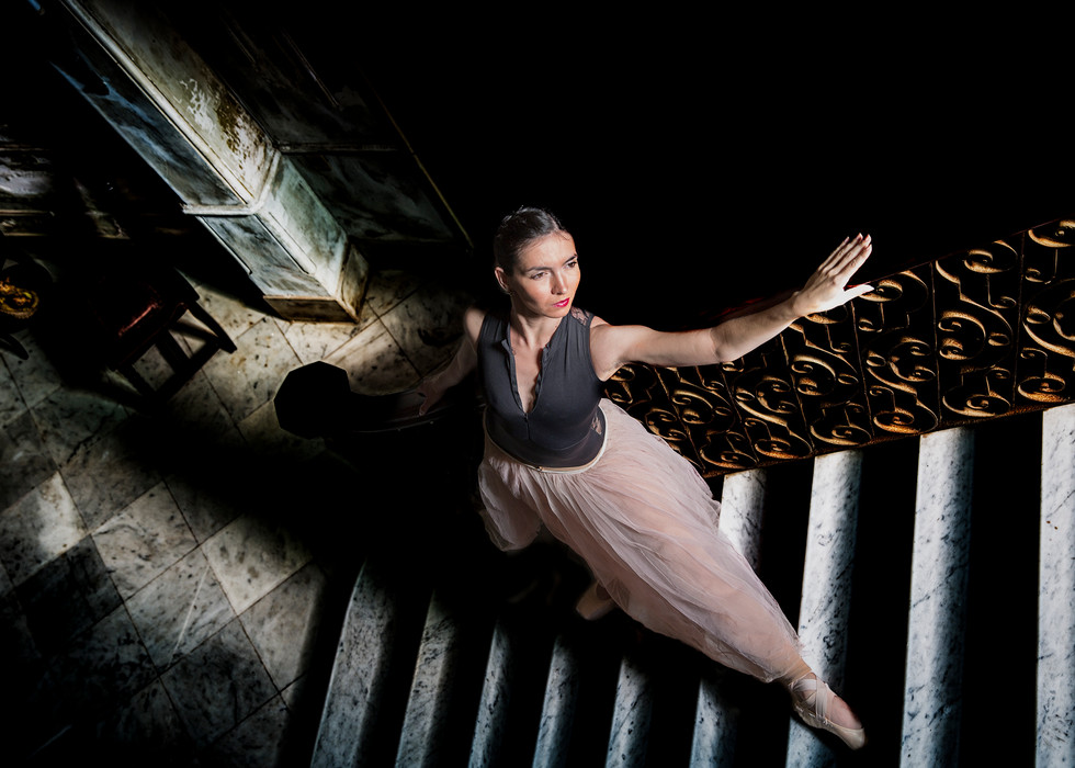 Ballerina on stairs, in shadows