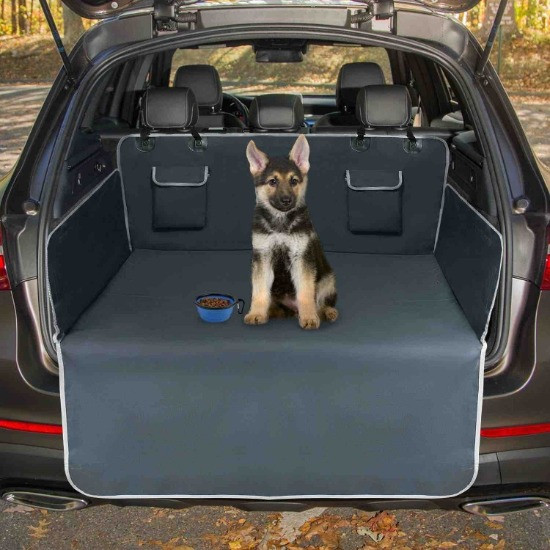 puppy sitting on a toozey grey car boot liner