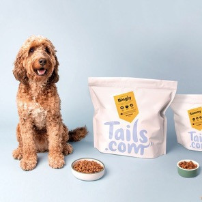 Cockapoo sitting with Tails.com delivered dog food packaging
