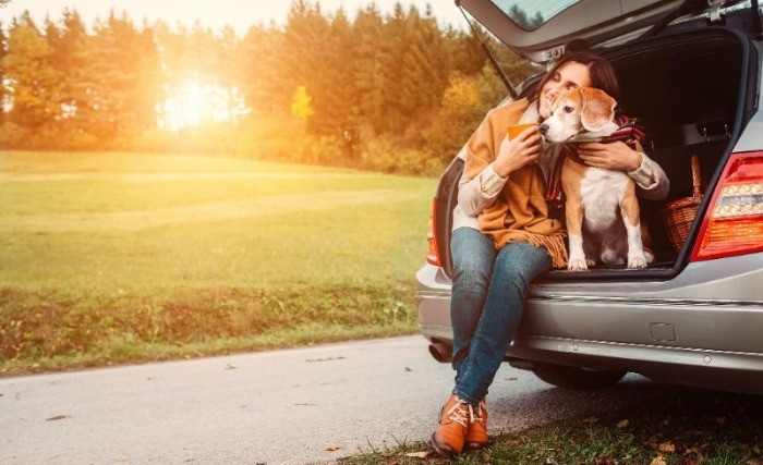 Girl sitting in open boot of her car with her dog in the countryside