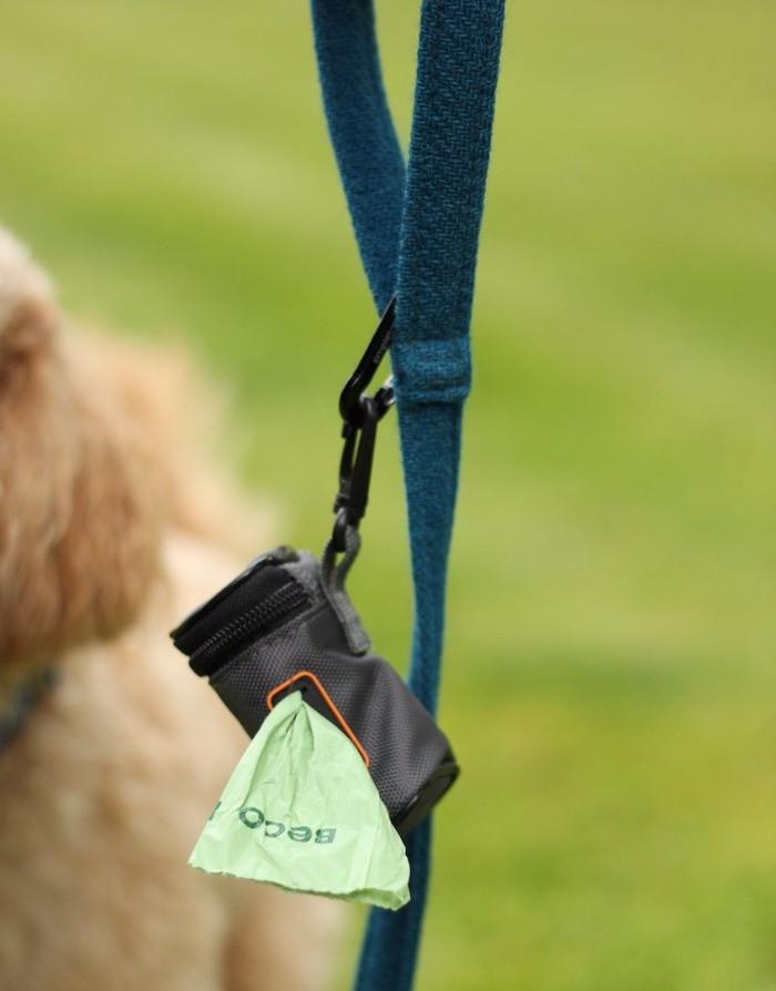 A Simpletome black and orange fabric poo bag holder on a teal dog lead
