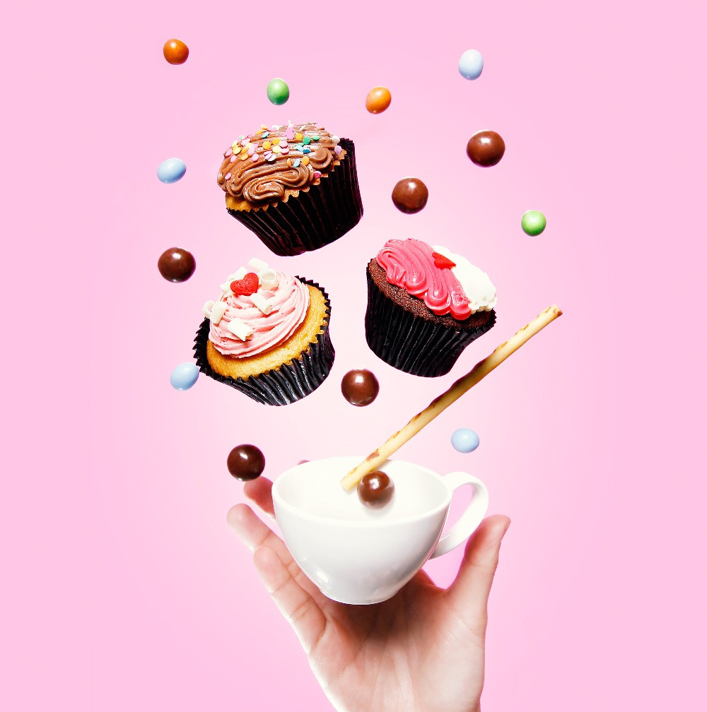 A hand holding a cup exploding with sweets and cupcakes