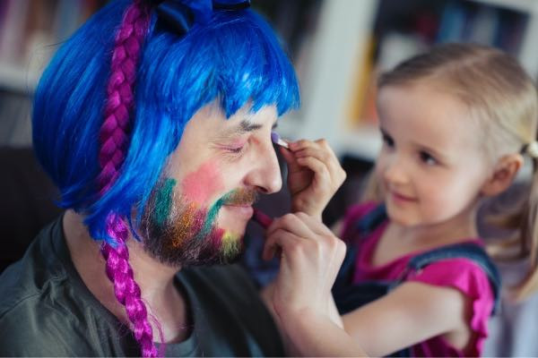 Little girl painting her daddy's face with faceprint