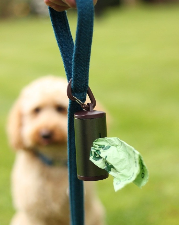 A dark green aluminium dog poo bag holder with a bag showing on a dog lead