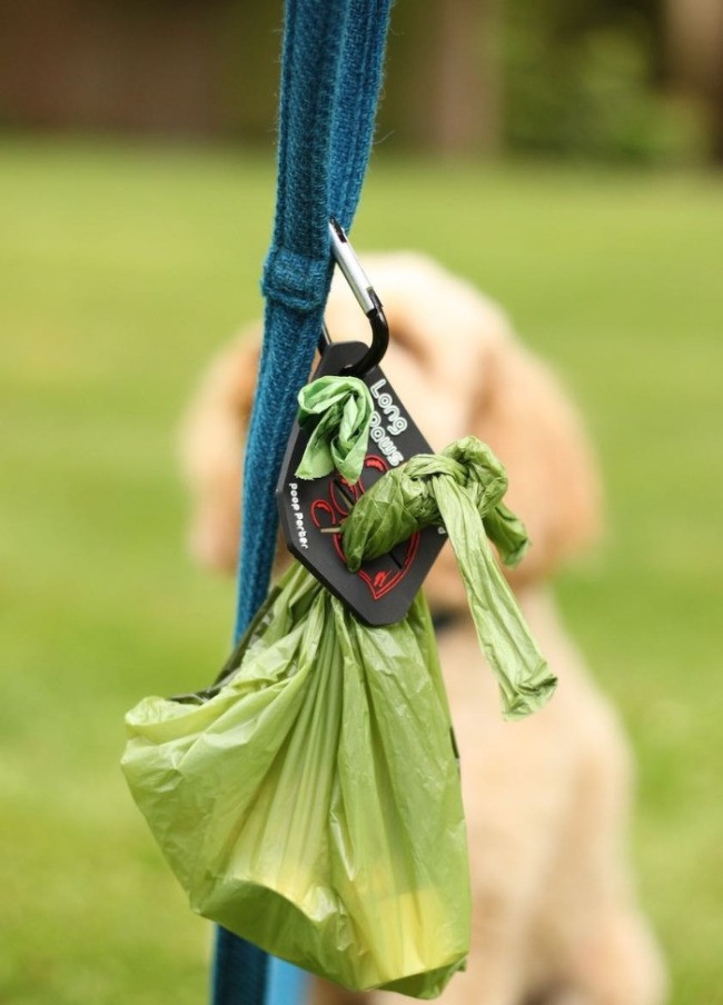 The Long Paws Poop Porter attacket to a dog lead with empty and full dog poo bags attached