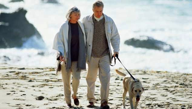 Old people keeping healthy on the beach with their dog