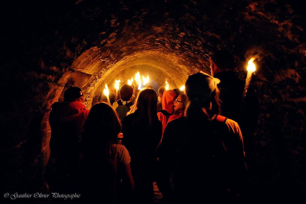 groupe de personnes avec des torches dans le tunnel du château-fort de Bouillon pendant une visite nocturne