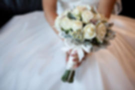 A bride is holding a wedding bouquet with white roses.