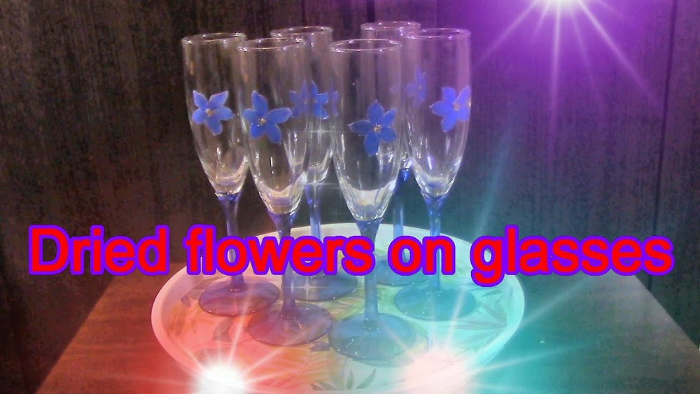 Pressed Flower Crafts on champagne glasses. Dried under press flowers of Delphinium on champagne glasses.